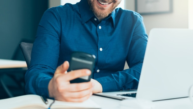 Cropped faceless smiling young man in casual wear looking at smartphone screen at workplace