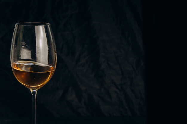 Cropped female hand holding a glass of white wine on a black background.  alcoholic drink closeup.