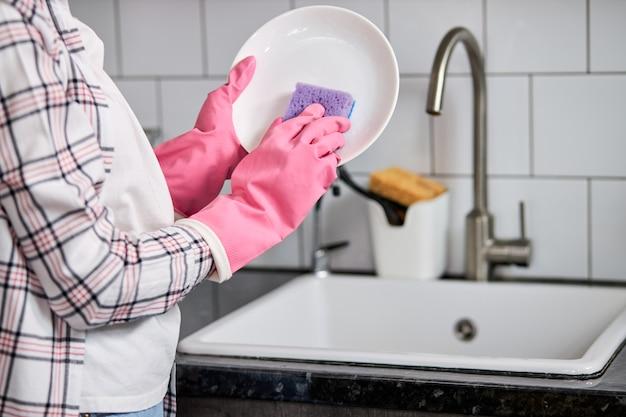 보라색 청소 스폰지와 흰색 접시를 세척하는 분홍색 보호 고무 장갑에 잘린 여성 손