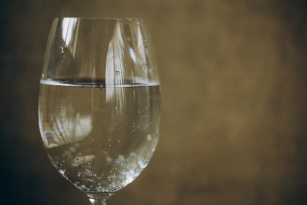 Cropped glass of white wine on a rustic wooden brown background. alcoholic drink closeup. copy space