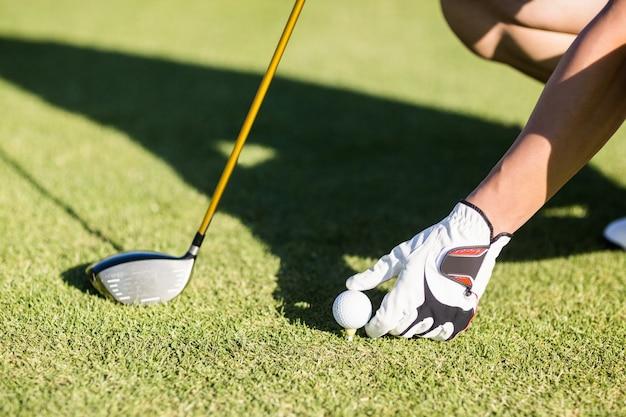 Укороченный гольфист, кладущий мяч для гольфа на футболку