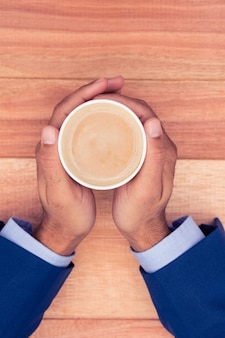 Cropped hand of businessman holding disposable coffee cup at wooden desk