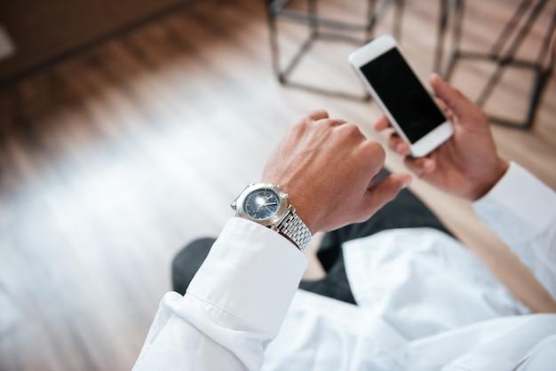 Обрезанный красивый бизнесмен, разговаривающий по телефону в офисе, смотрит на часы