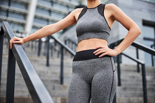 Cropped head of athletic slim female demonstrating perfect abdominal after workout while standing on stairs outdoors
