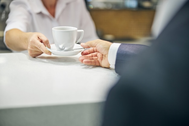 잘린 머리는 양복을 입은 남자에게 차 한 잔을 주문하는 바텐더 손을 닫습니다.