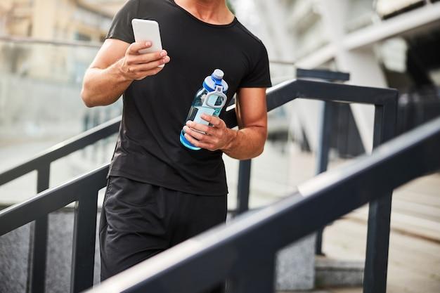 물을 들고 도시에서 스마트 폰 운동에 메시징 운동 남자의 자른 머리