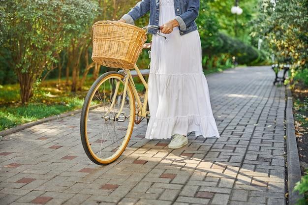 빈티지 자전거로 여름 녹색 대로를 걷고 있는 흰 드레스를 입은 여성의 자른 머리