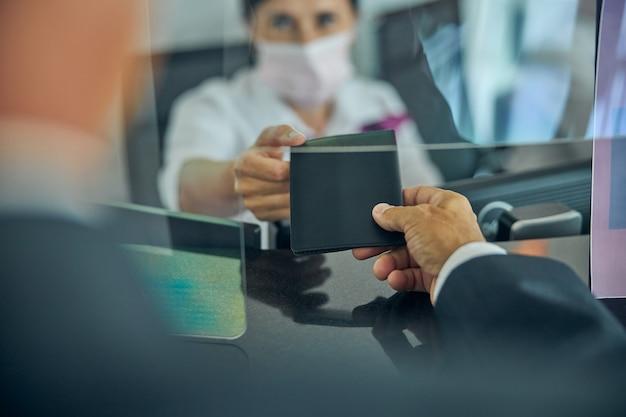 등록 데스크에서 유리 뒤에 있는 여성에게 여권과 티켓을 제공하는 정장을 입은 남성의 자른 머리