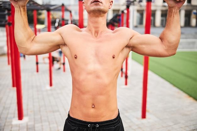 野外でスポーツグラウンドで運動している筋肉質の若い男のトップレスコアのトリミングされた頭