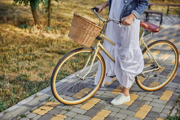 복고풍 자전거와 함께 길에 서 있는 흰 드레스를 입은 성인 여성의 자른 머리 초상화