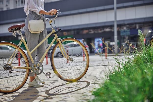 유명한 역사적 장소를 걷고 있는 복고풍 도시 자전거를 탄 아름다운 여성의 머리 초상화