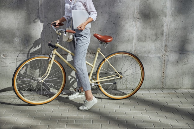 회색 배경에 격리된 손에 회색 노트북을 들고 복고풍 도시 자전거를 들고 있는 비즈니스 여성의 자른 머리 초상화