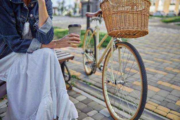 야외에서 나무 벤치에 앉아 있는 동안 손에 종이컵의 커피를 들고 있는 여성의 자른 머리 초상화