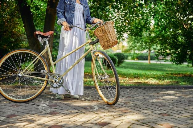 녹색 공원을 통해 복고풍 자전거와 함께 걷는 흰색 드레스와 데님 재킷 여성의 자른 머리 초상화