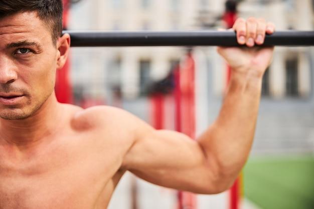 屋外のスポーツグラウンドのクロスバーで背中のプルアップをしている筋肉質の男性のトリミングされた頭の肖像画