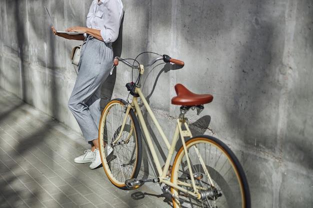 야외에서 노트북 작업을 하는 흰색 셔츠와 회색 바지를 입은 세련된 여성이 있는 복고풍 도시 자전거의 자른 머리 초상화