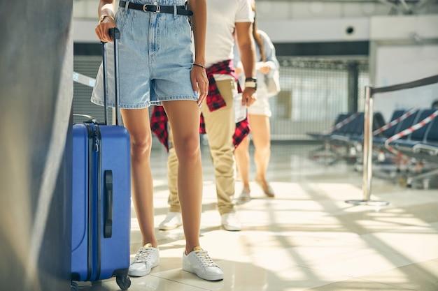 비행기 탑승 승객을 기다리는 가방이있는 관광 그룹의 자른 머리 초상화