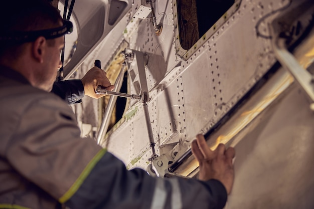 Cropped head side view portrait of aviation engineer working on the landing gear compartment with special tools