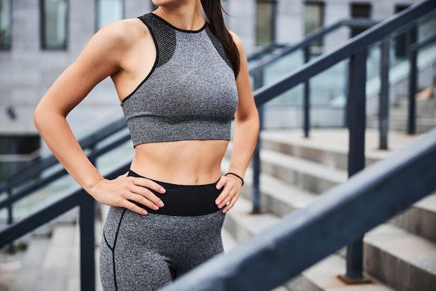 Cropped head of slim female in sportwear standing on stairs in city centre while going training