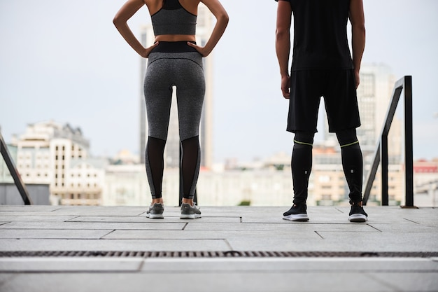Cropped head of slim woman and man standing together after training and looking at cityscape