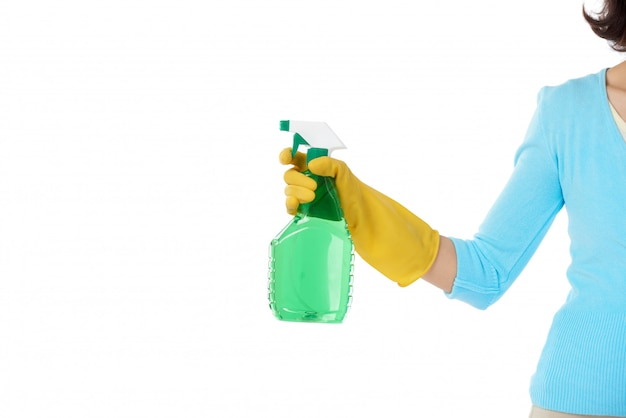 Cropped housemaid standing with stretched hand holding the detergent spray bottle