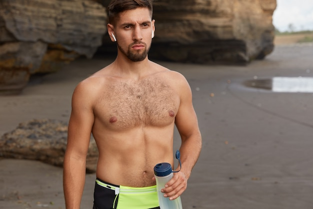 Cropped image of active jogger or fitness instructor takes break and drinks water