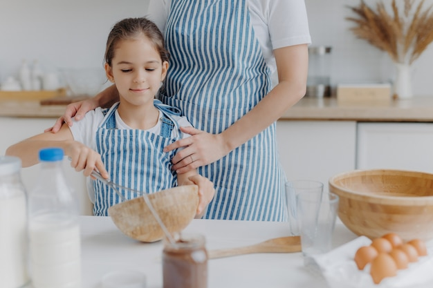 Cropped image of affectionate mother in apron embraces daughter who learns how to make pasty