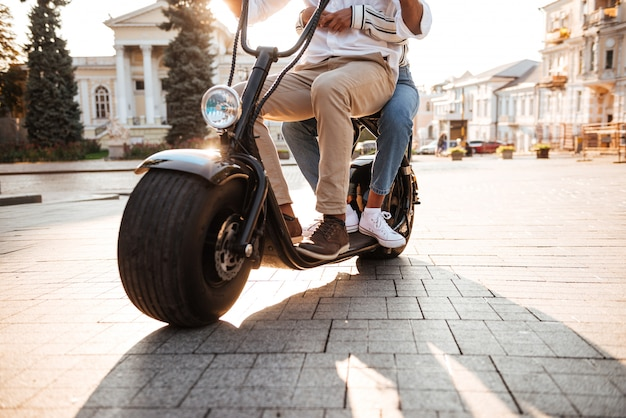Cropped image of african couple rides on modern motorbike on the street
