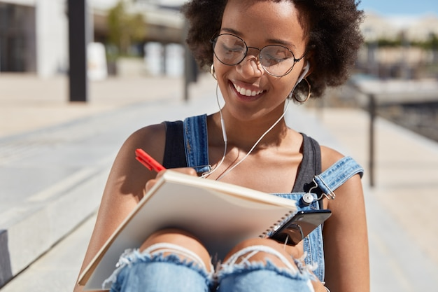 Cropped image of attractive cheerful young female artist makes creative notes in notepad, wears spectacles, enjoys nice track in earphones connected to mobile phone, has positive expression.