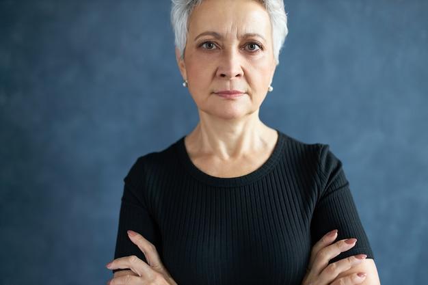 Immagine ritagliata di attraente femmina europea di mezza età con elegante taglio di capelli corto che ha un'espressione facciale seria rigorosa, tenendo le braccia conserte in postura chiusa, essendo testarda.