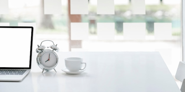 Cropped image for background with tablet and keyboard, alarm clock and coffee cup on white table, copy space.