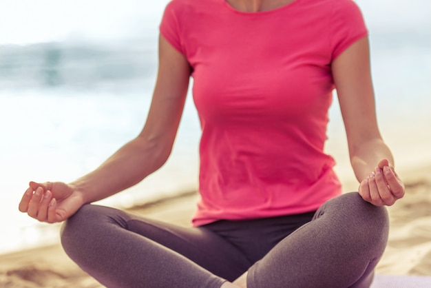 Cropped image of beautiful girl in sport clothes meditating.