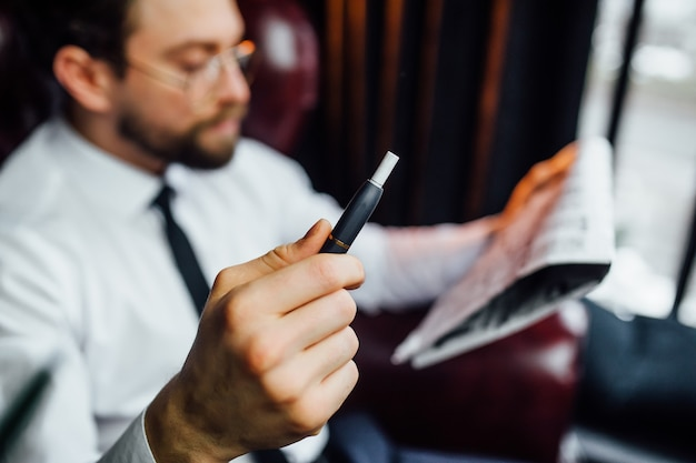Cropped image, business man resting on armchair in luxury room, man smoking cigar in his house.