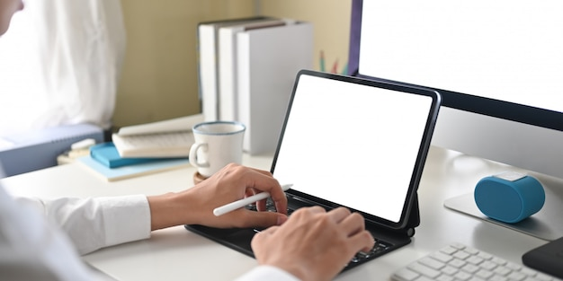 Cropped image of a businessman is using a white blank screen computer tablet at the white working desk.