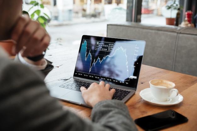 Immagine potata dell'uomo d'affari che si siede dalla tavola in caffè e che analizza gli indicatori