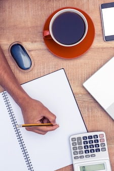 Cropped image of businessman writing on notebook by coffee at desk in office