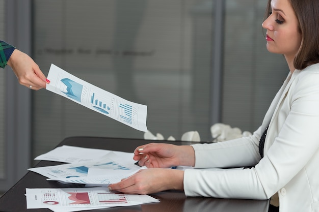 Cropped image of businesswoman giving progress chart to colleague at desk in office.
