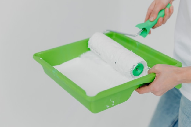 Cropped image of busy woman stands with tray and paint roller