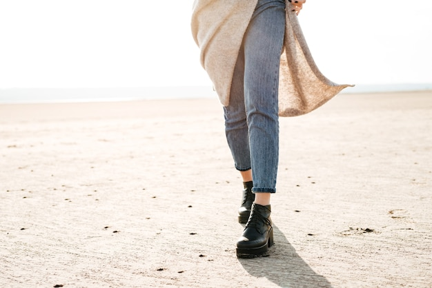 Cropped image of a casual woman in jeans walking across the beach in sunlight
