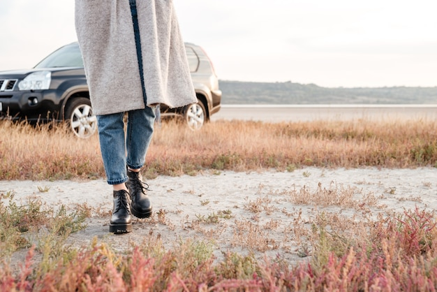 Cropped image of a casual woman walking outside with car on background