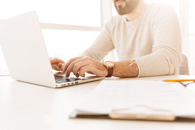 Cropped image of caucasian man  wearing wrist watch and casual clothing working on laptop, while sitting at table indoor