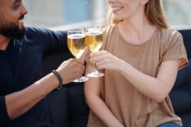 Cropped image of cheerful young couple toasting with glasses of champage