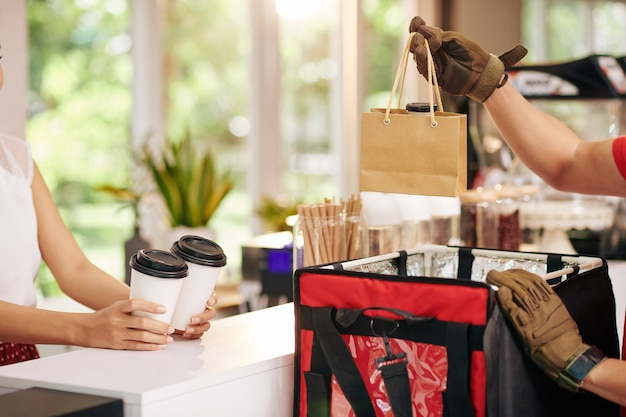 Cropped image of courier putting fresh non-dairy yogurt and cups of take away coffee in bag to deliver order from local cafe