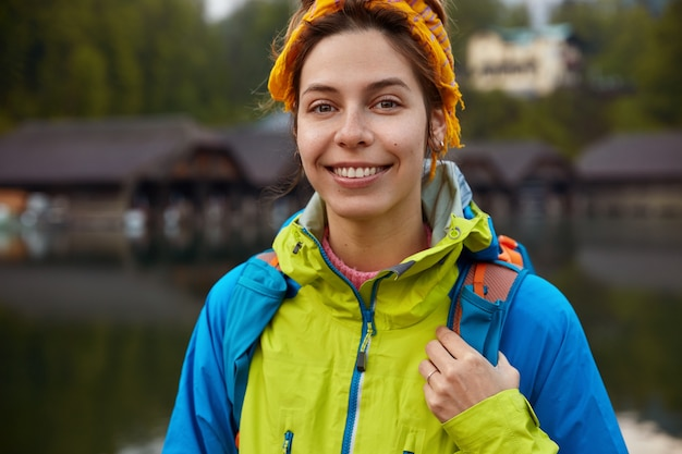 Cropped image of delighted woman with toothy smile, wears casual jacket, carries rucksack
