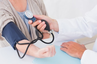 Cropped image of doctor checking patients blood pressure
