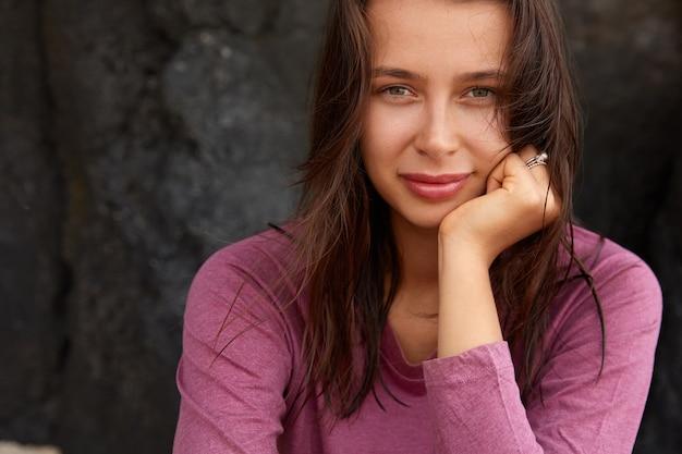 L'immagine ritagliata della donna europea tiene il mento, ha i capelli scuri e la pelle sana