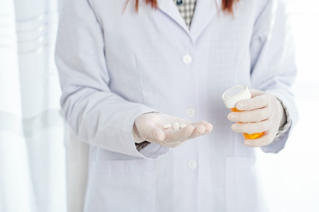 Cropped image of female doctor offering hadnful of pills