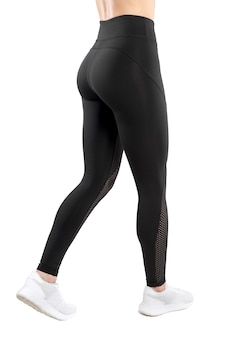 Cropped image of a female figure in tight black leggings take a side step, isolated white background. vertical view.