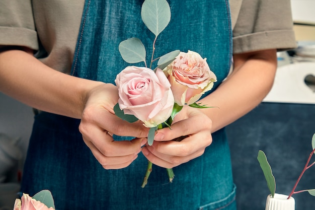 Cropped image of female florist at work. arranging various flowers in bouquet. close up flowers in hand. florist workplace. floral, decoration studio. professional concept. copy space for design