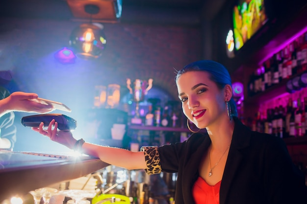 Cropped image female worker accepting payment from customer through nfc in bar